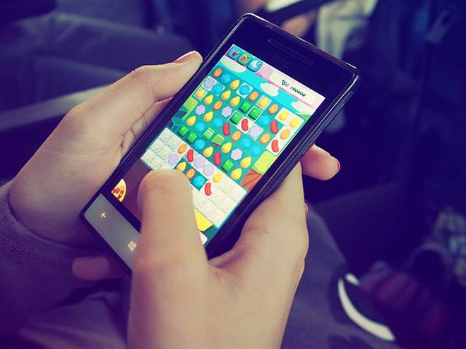 In-Game Purchases: Person playing Candy Crush Saga on a phone.
