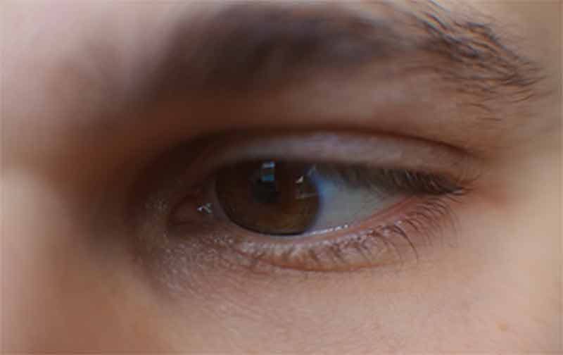 Sex Ed Curriclum: Close-up of young man's eye looking at screen